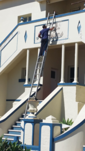 How not to use a ladder image. Not tied off and no fall protection.